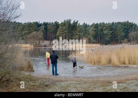 Frensham Teiche im Winter mit dem See zugefroren und Menschen neben dem See und spielen auf dem Eis - Stockfoto