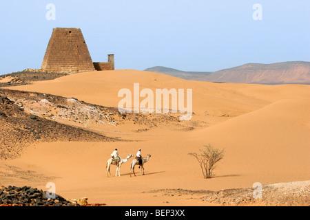 Pyramiden von Meroe und zwei nubischen Männer gekleidet in Thawb Reiten Dromedare in der nubischen Wüste des Sudan, - Stockfoto