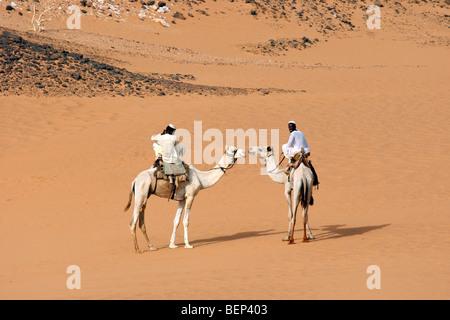 Zwei nubischen Männer gekleidet in Thawb Kamelreiten Dromedar (Camelus Dromedarius) in der nubischen Wüste des Sudan, - Stockfoto