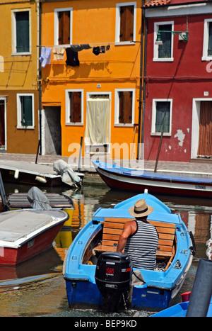 Mann im Motorboot und bunten Häusern in Burano, Venedig, Italien - Stockfoto