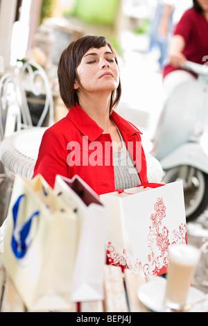 Frau in einem Straßencafé nach dem Einkauf - Stockfoto