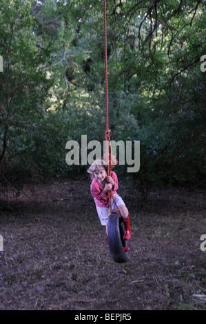 Ein sechs Jahre altes Mädchen auf einem Baum Seil schwingen - Stockfoto