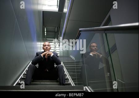 Mann sitzt auf Treppenstufen - Stockfoto