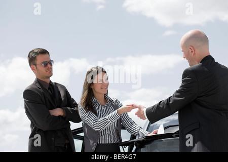 man Unterzeichnung Vertrag auf Rückseite Auto - Stockfoto