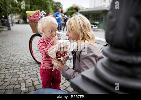 Kleine Mädchen und Mutter Essen Kirschen - Stockfoto