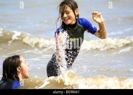 Kinder plantschen im Meer tragen Neoprenanzüge - Stockfoto