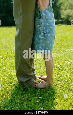 der Vater und der Tochter Beine, die Tochter barfuss auf der Oberseite des Vaters Füße in Nahaufnahme - Stockfoto