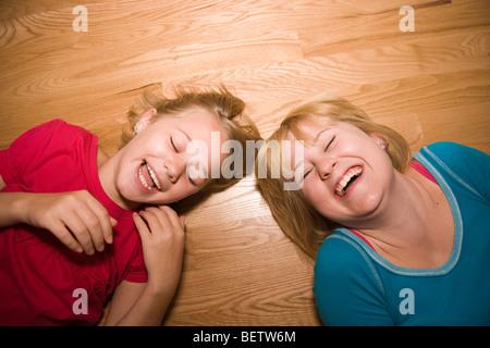 Zwei Schwestern Lachen hysterisch auf einen hölzernen Fußboden, 11 und 14 Jahren - Stockfoto