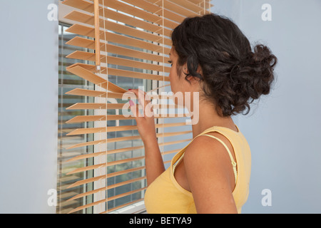 Junge Frau, Blick aus dem Fenster durch Vorhänge Stockfoto