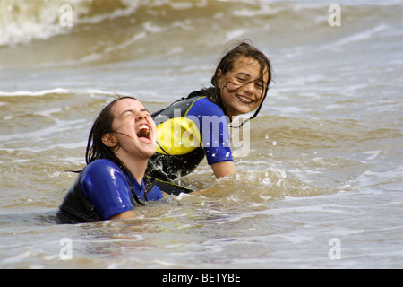 zwei Mädchen, die Schwimmen im Meer in Neoprenanzüge eine großartige Zeit spielen in den Wellen Stockfoto
