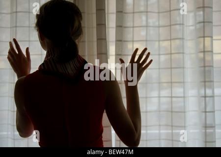 Frau suchen Fenster Stockfoto