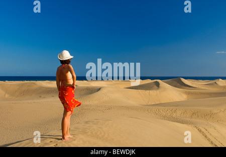 Frau steht auf einer Düne mit Blick auf das Meer, Maspalomas, Gran Canaria, Spanien, Rückansicht - Stockfoto