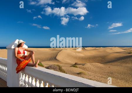 Frau sitzt auf einem Zaun, Blick auf die Sanddünen, Maspalomas, Gran Canaria, Spanien - Stockfoto