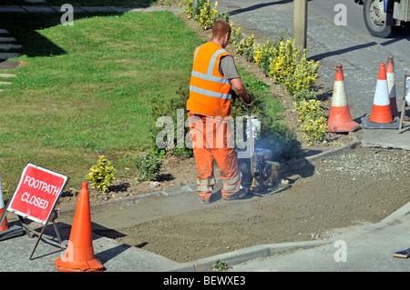 Arbeiter, die Teilnahme an Gehweg Pflaster Reparaturen in Wohnstraße - Stockfoto