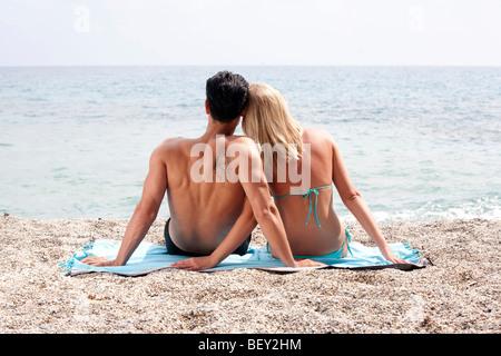 junges Paar sitzt direkt am Meer - Stockfoto
