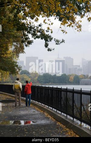 Zwei Passanten im Central Park entlang der Jacqueline Kennedy Onassis Reservoir, mit Skyline von New York City in - Stockfoto