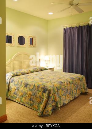Grün lackiert Schlafzimmer in einem gut zugewiesenen Strandhaus. Spiegel an der Wand und einem dunklen blauen Vorhang - Stockfoto