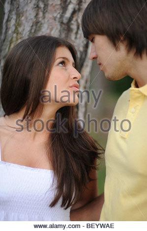 Junge Paar küssen an einem Baum - Stockfoto