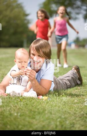 Vater mit Kindern auf einer Wiese - Stockfoto