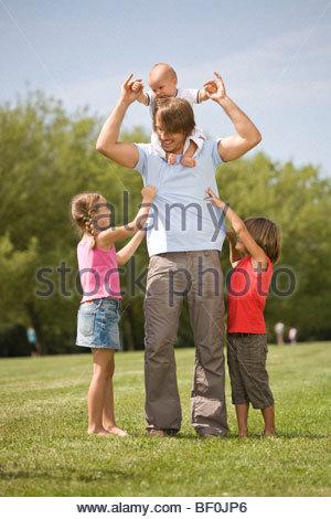 Vater mit seinen Kindern auf einer Wiese - Stockfoto