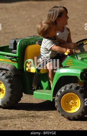 Junge Kinder Fahrspaß Spielzeug-Traktoren auf auf einer provisorischen Traktor-Rennstrecke im Irvine Regional Park - Stockfoto