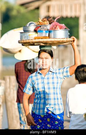 Frau mit Korb auf dem Kopf, Verkauf von Lebensmitteln, Yangon, Myanmar. - Stockfoto