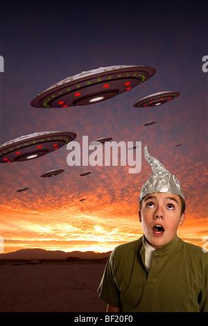 Ein Junge mit Alufolie Hut beobachtet ein Geschwader von UFOs. - Stockfoto