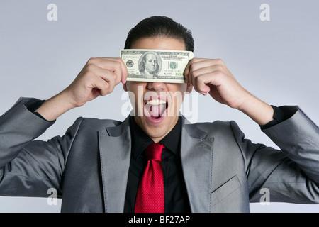 Geschäftsmann mit Dollarnoten jungen Anzug und Krawatte auf grauem Hintergrund - Stockfoto