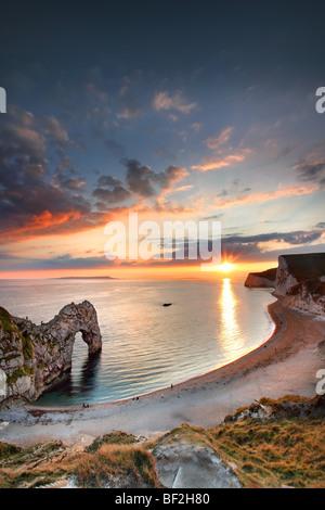 Durdle Door bei Sonnenuntergang mit Menschen am Strand, Dorset. - Stockfoto