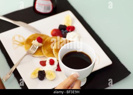 Person mit einer Tasse Kaffee über Pfannkuchen - Stockfoto