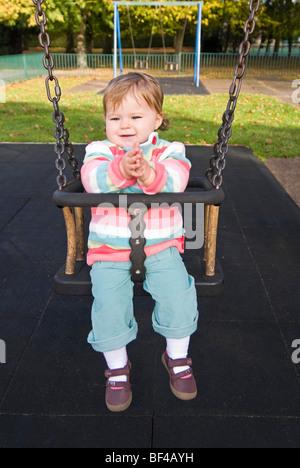 Vertikale Nahaufnahme Portrait eines kleinen Mädchens lächelnd und klatschten im Park in der Sonne auf einer Schaukel - Stockfoto