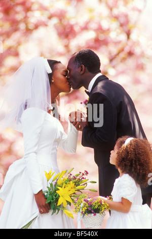 Eine Braut und Bräutigam küssen sich während ihrer Hochzeit unter einem Baldachin von Kirschblüten. - Stockfoto