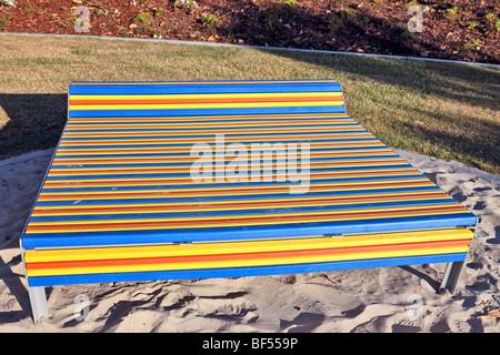 Parkbank mit Muti farbige Latten - Stockfoto