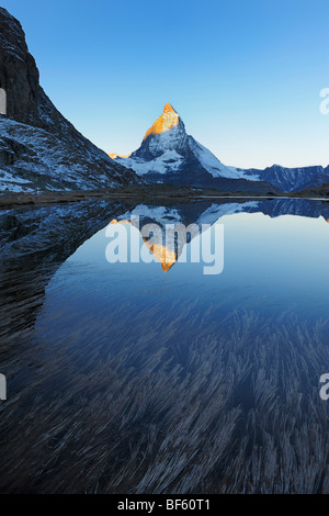 Matterhorn bei Sonnenaufgang im Winter mit Reflexion im Riffelsee, Zermatt, Wallis, Schweiz, Europa - Stockfoto