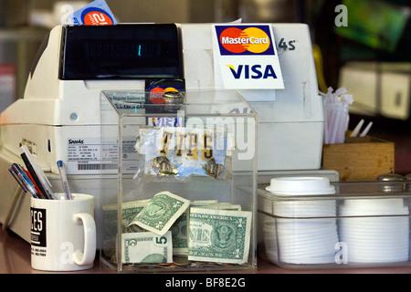 Geld in Tipp-Glas neben Registrierkasse - Stockfoto