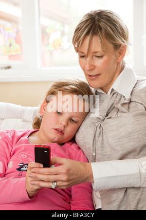 Mutter hilft Mädchen Senden von Textnachrichten auf dem Handy - Stockfoto