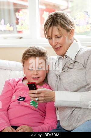 Mutter hilft jungen Tochter Kurzmitteilungen auf dem Handy - Stockfoto