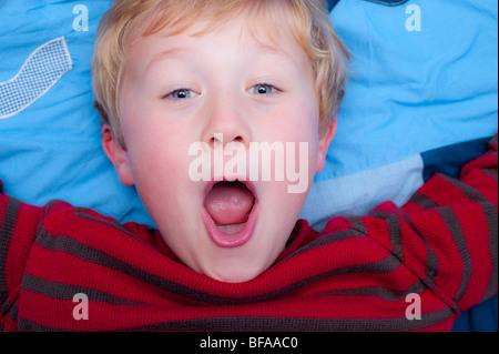 Ein Model Release Bild eines sechsjährigen Jungen ziehen ein dummes Gesicht drinnen im Vereinigten Königreich - Stockfoto