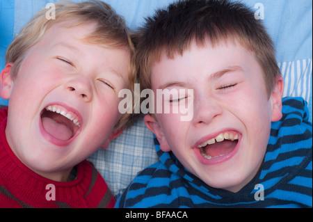 Ein Model Release Bild von zwei Brüder (10 und 6) Lachen drinnen im Vereinigten Königreich - Stockfoto
