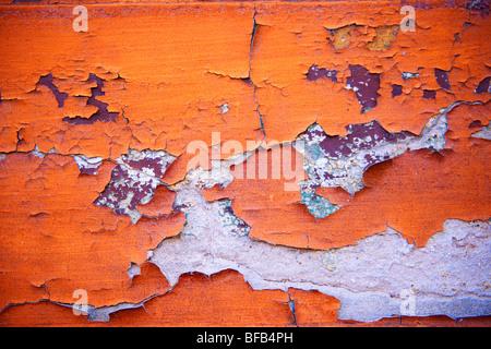 Nahaufnahme der abblätternden orangen Farbe an einer Wand - Stockfoto