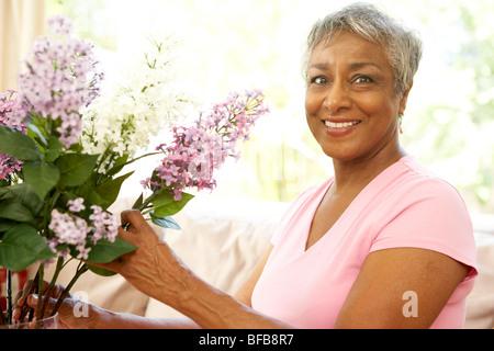 Senior Woman Blumenarrangements zu Hause - Stockfoto