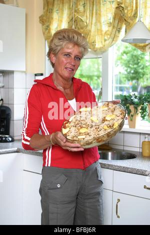 Reife Frau zeigt stärkehaltige Lebensmittel essen in der Küche. - Stockfoto