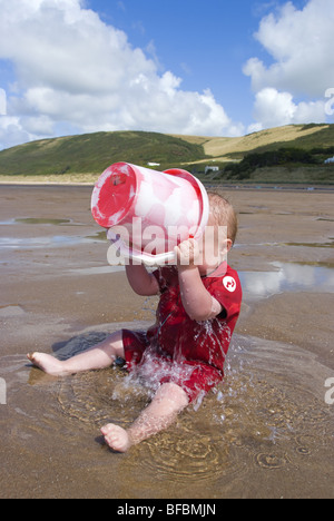 Ein Kleinkind gießt Wasser über sich selbst in den Untiefen auf Puttsborough Sand North Devon UK - Stockfoto
