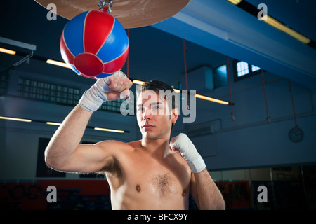 junge Erwachsene Mann schlägt Beinsack im Fitness-Studio. Textfreiraum - Stockfoto