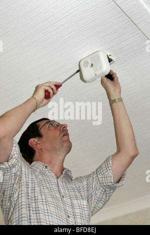 Männliche Elektriker behebt ein Rauchmelder an der Decke ein Haus - Stockfoto