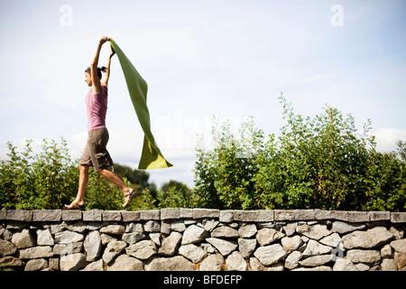 Eine Frau behauptet, ihre grüne Yogamatte einen Umhang ist beim laufen auf einem Stein Felsvorsprung. - Stockfoto