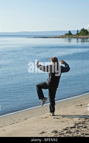 Person, die sich darin üben, Tai-Chi in den frühen Morgenstunden am Strand von Cap-Aux-Ojes in Charlevoix, Quebec, - Stockfoto