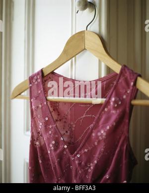 Nahaufnahme von Perlen rot Chiffon dress auf hölzernen Kleiderbügel - Stockfoto