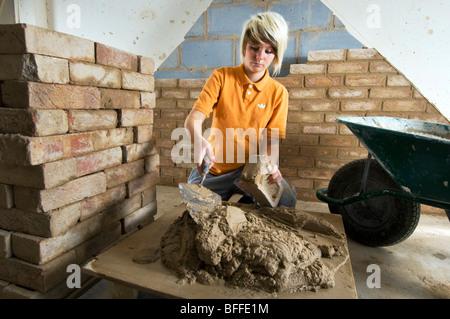 Lernen praktische Ziegelmauerwerk in einer City College Studentin - Stockfoto