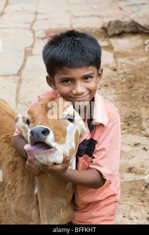 Jungen umarmen ein Kalb in einer ländlichen indischen Dorf. Andhra Pradesh, Indien - Stockfoto